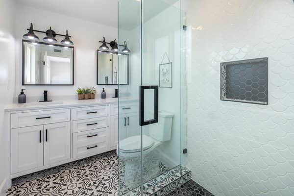 Updated bathroom with artistic pattern tile flooring and glass enclosed shower