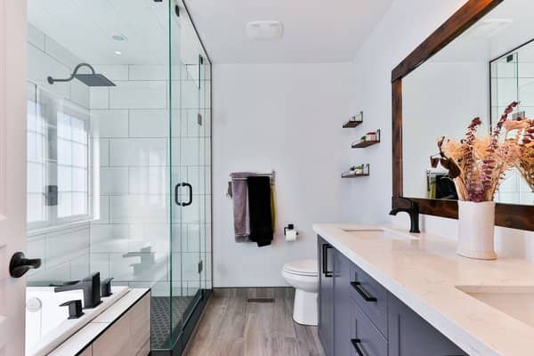 Bathroom remodel project with glass shower enclosure and weathered gray flooring